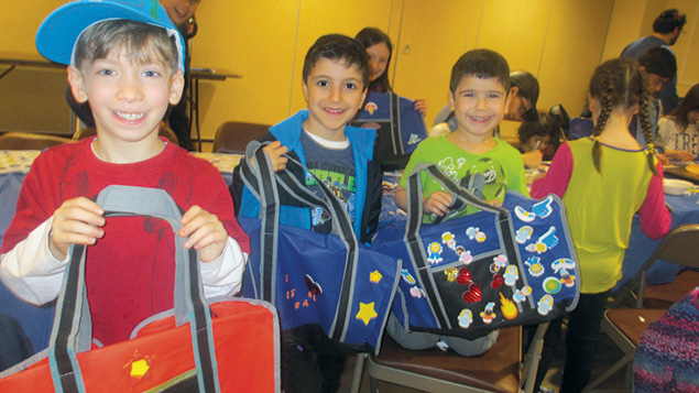 To earn letters in a Torah scroll, children make duffel bags for homeless children.