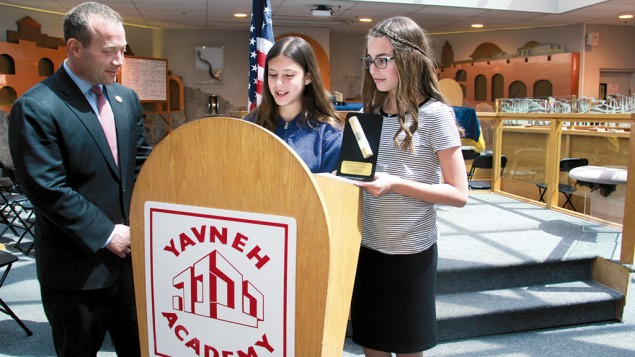 Congressman Gottheimer accepts a presentation from two Yavneh students at the assembly.