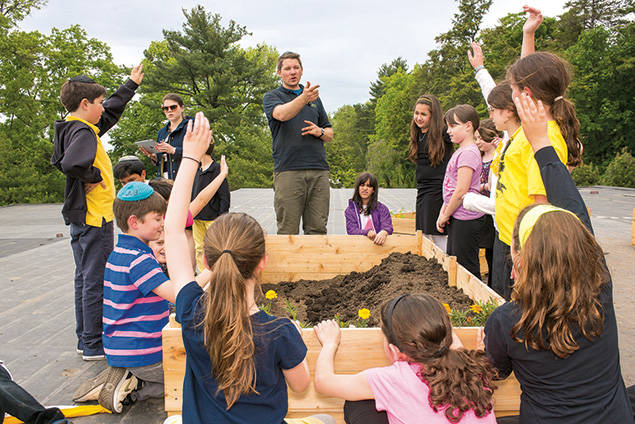 SAR students are instructed in the preparation of soil for planting a garden.
