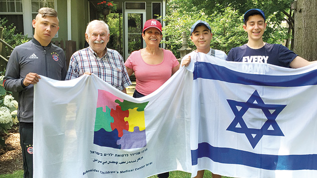 Campers and their hosts hold flags of Israel and the Schneider Children's Medical Center, where the campers have received medical care.
