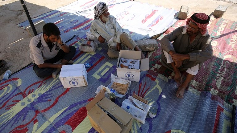 Displaced Iraqis, who fled the fight between Iraqi forces and the Islamic State in Tal Afar, sit inside a tent next to boxes of medical aid at the Badush camp on August 25, 2017. (AFP Photo/Ahmad Al-Rubaye)