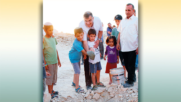 Recently, Mr. Hatuel, two of his younger children, and other friends look on as the reconstituted community lays a cornerstone for its new synagogue.