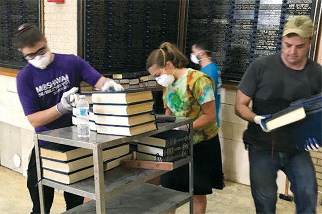NCSY volunteers clean synagogue books damaged in the hurricane.