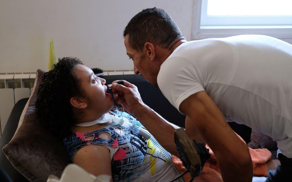 حمدي آمن يضع أحمر الشفاه على ابنته ماريا التي أصيبت بالشلل في منزلهم في حي بيت صفافا بالقدس في 23 أغسطس / آب 2017. (Judah Ari Gross/Times of Israel)
