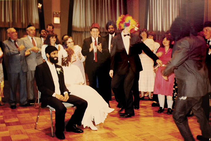 Meylekh and Gitl sit at their wedding while their guests dance to amuse them.