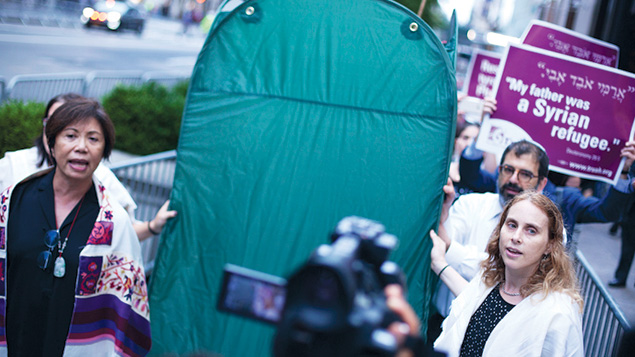 """In New York, rabbis marched with a portable sukkah to support immigrants Two dozens rabbis, members of T'ruah: The Rabbinic Call for Human Rights, carried a portable sukkah that they erected outside Trump Tower. The gesture was meant as an act of protest against the president's stance on immigrants and refugees. """"Sukkot teaches us that what protects us is the community we build, not the walls or barriers we construct,"""" said Rabbi Jill Jacobs, T'ruah's executive director. """"What makes America strong is the diverse group of people who come here seeking refuge and who build families and communities here."""" HIAS, the Jewish immigration advocacy agency, was a co-sponsor of the march."""