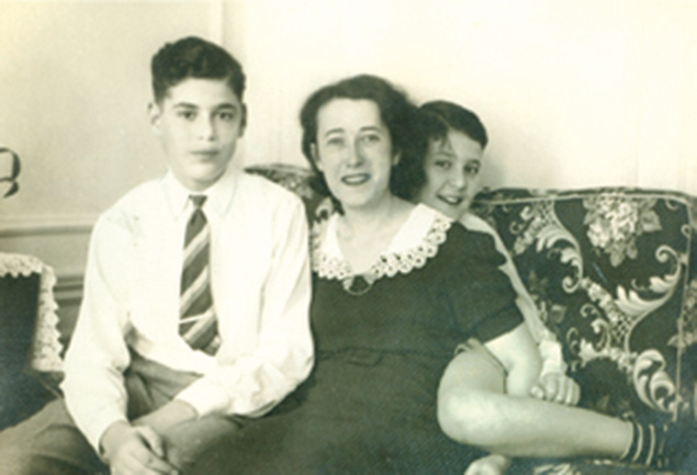 A young Peter Adler hides behind his mother and his brother, Frank, in 1940.