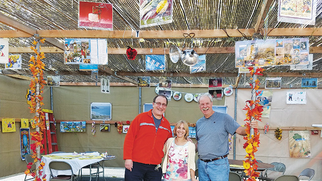 Temple Beth Sholom of Fair Lawn members Fred and Denise Holzsager and Richard Michaelson check out the weekend's efforts from the shul's sukkah decorating party. (Courtesy TBS)