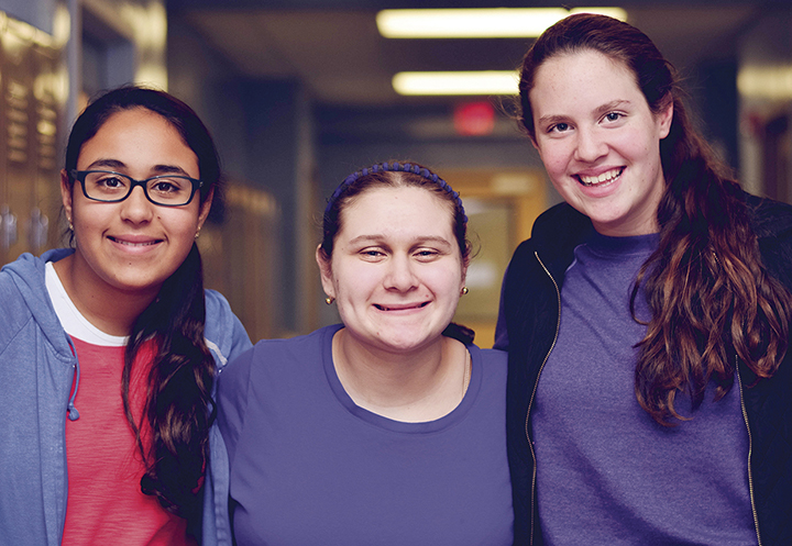 Kayla Murad, Yaffa Elyakin, and Arielle Mandel smile together at a New Jersey Yachad program.
